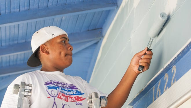 13-year-old high school freshman Chris Johnson, of Natchez, MS, paints a house in Pensacola, FL on Monday, July 18, 2016.  Fifty teens from Catholic HEART Workcamp working in association with Pensacola Habitat for Humanity are volunteering in town this week doing revitalization projects.