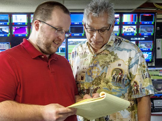 Austin Bayliss, television production specialist, and John Hernandez, television commentator and horseman's liaison, not Prairie Meadows employees, help get ready for activities.