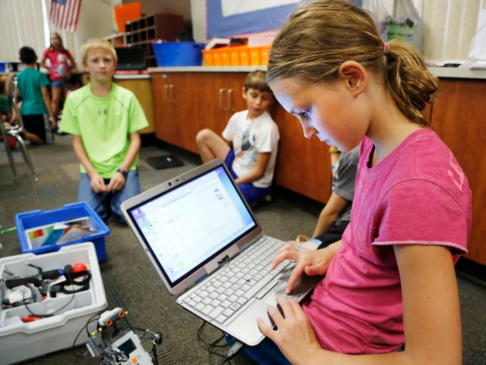 "Fifth grade student Elizabeth Ricks uses a laptop computer to program a LEGO robot Friday, August 22, 2014, in Beau Scott's 4/5 high ability classroom at Dayton Elementary School. Scott has a ""transparent classroom"" where he keeps a blog to keep parents and students updated on what is happening in his class."