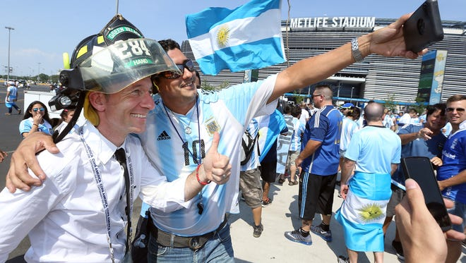 Firefighter Alfredo Hand of Chatham takes a selfie with Argentinian sports journalist Juan Cortese wearing his Green Village fire helmet during the pre-game tailgating in the parking lot of MetLife Stadium before the historic Argentina vs. Chile final of the 100th anniversary Centennial Copa America at MetLife Stadium, June 26, 2016, East Rutherford, NJ