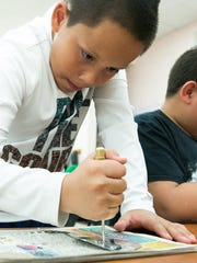 Fairacres Elementary School student Steven Camunez, 11, works on punching tin on Thursday during a special art class held by fifth generation tin smith Jason Younis y Delgado.