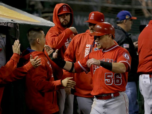 Los Angeles Angels' Kole Calhoun (56) is congratulated after scoring against the Oakland Athletics during the fifth inning of a baseball game in Oakland, Calif., Wednesday, April 5, 2017. (AP Photo/Jeff Chiu)