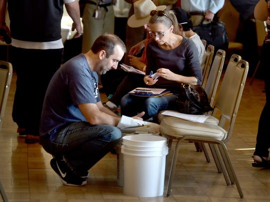 Michael and Lyn Cerminaro, who lost their Ventura home to the Thomas Fire, fill out paperwork at a local assistance center at the Poinsettia Pavilion in Ventura on Wednesday. Several local and state agencies were on hand to offer information and services to victims of the blaze.