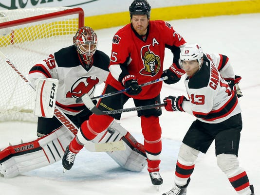 New Jersey Devils goaltender Cory Schneider (35) watches for the puck as Ottawa Senators' Chris Neil (15) and Devils' Mike Cammalleri (13) work for position during the third period of an NHL hockey game Wednesday, Dec. 30, 2015, in Ottawa, Ontario. (Fred Chartrand/The Canadian Press via AP)