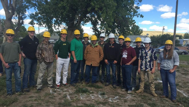C.M. Russell High School construction students stand on the site of what will be the 38th High School Home.