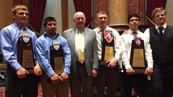 State Sen. Wally Horn, D-Cedar Rapids, center, poses with members of the Grand View University championship wrestling team on Tuesday at the Iowa Capitol.