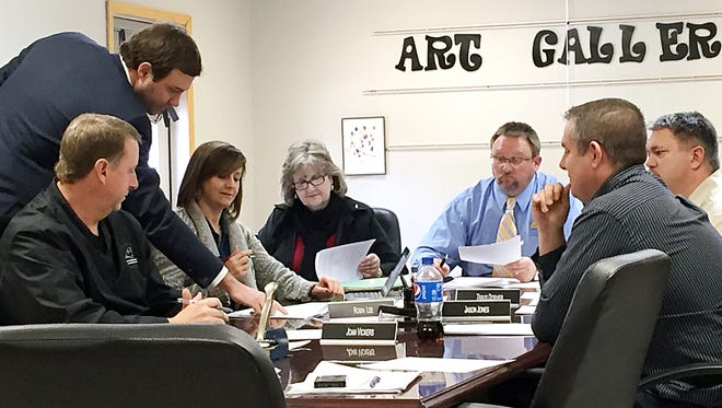 Members of the Yellville-Summit School Board sign papers Tuesday for a bond sale. The refunding will save $164,929 during its first three years.