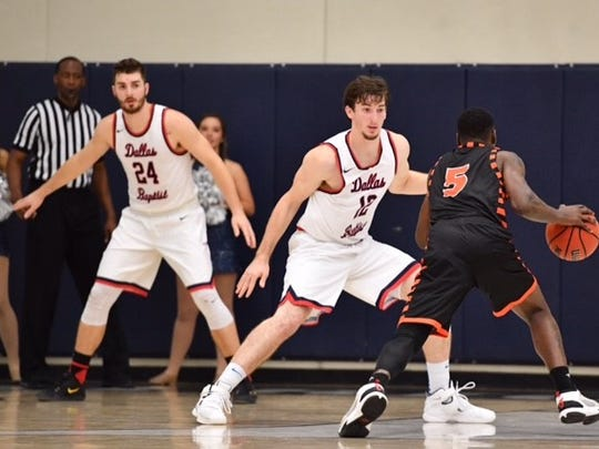 Dallas Baptist's J.T. Harris guards an opponent while brother Brayden Harris (24) looks on.