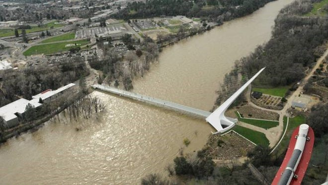 A muddy and swelling Sacramento River passes under the Sundial Bridge this week in Redding.