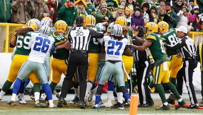 A fight breaks out between Green Bay Packers and Dallas Cowboys players during the second half of an NFL divisional playoff football game Sunday, Jan. 11, 2015, in Green Bay, Wis.