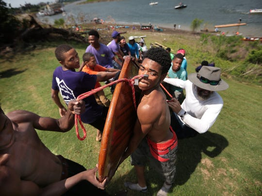 Trayvius Butler (center) and other kids from the Carpenter Art Garden recently competed in a canoe and kayak race on the Mississippi.