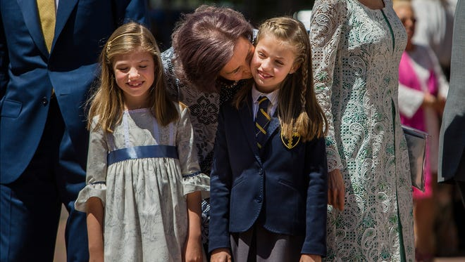 Spain's King Felipe VI's mother Sofia, center, kisses Crown Princess Leonor as Princess Sofia, left, smiles, during Princess Leonor's first communion in Madrid, Spain, Wednesday, May 20, 2015.