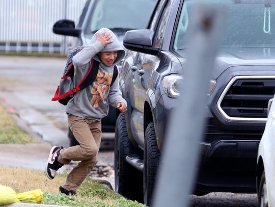 Jose Rodriguez, 7, runs to his car at Evans Elementary