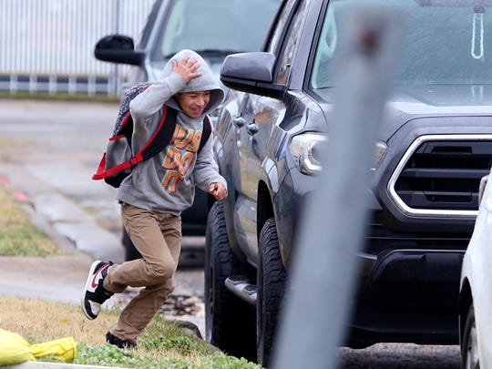 Jose Rodriguez, 7, runs to his car at Evans Elementary School on Tuesday, Jan. 16, 2018. School was released early due to expected bad weather.