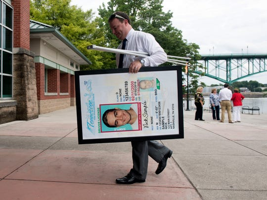 We Moster, deputy communications director for Tennessee's Department of Safety and Homeland Security, carries a poster-sized sample of the vertical licenses to be issued to people under 21. The new law was announced in a news conference at Volunteer Landing on Monday, July 2, 2018.