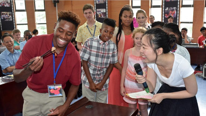 Students in MTSU's 2016 delegation to China watch curiously Tuesday as Elijah Rachell, 16, tastes a traditional Hangzhou dish. The tasting was part of a welcome ceremony for the 28-member group of mostly Rutherford County students, parents and teachers who joined the fifth annual exchange between the university and the Dongcheng Educational Group.