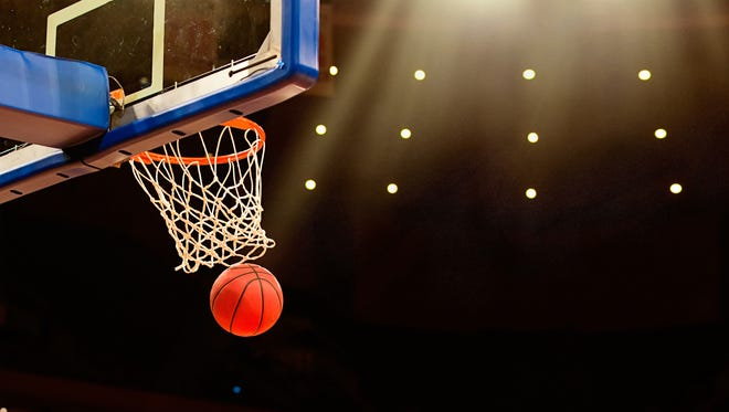 A ball swishes through the net at a basketball game in a professional arena