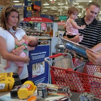 Laurie and Andy Follweiler, with their children, Jillian, 2 months, and Claire, 21 months, stock up on hurricane supplies at Lowe's in preparation for Tropical Storm Fay in south Fort Myers on Saturday August 16, 2008.