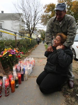 Raymond Antonio Ureña hugs his niece, Marisol Perez, on Oct. 30 2013, in front of the Mount Vernon, N.Y., home where four of their family members died in a house fire.