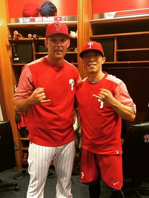 """Phillies first baseman Rhys Hoskins (left) and Korean language interpreter Derrick Chung show """"stingers up"""" as former teammates with the Sacramento State Hornets."""