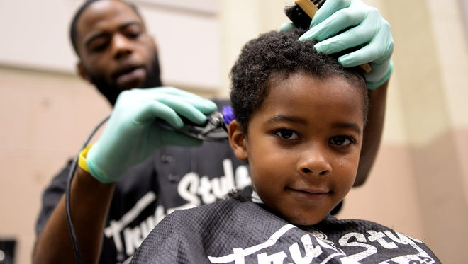Dre Cousey, 7, gets his hair cut by Rodrick Walton, of True Styles and Fades, Monday, August 31, 2015, at the annual Kids Connect event at the Lansing Center. The event offered hair cuts, eye and dental exams, immunizations, supplies and more for local school children.