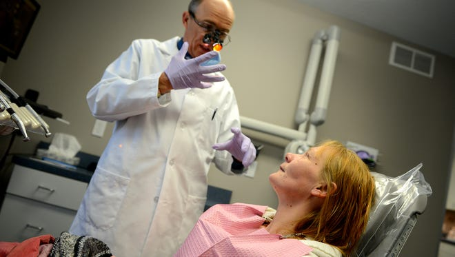 Dr. Tim Zielinski speaks with Grace Harry during a checkup  in Mason. Harry is getting dental care after decades of no care. She estimates she's been to urgent care with toothaches a dozen times and put on antibiotics. Zielinski helps patients like Harry through the Healthy Michigan Plan.