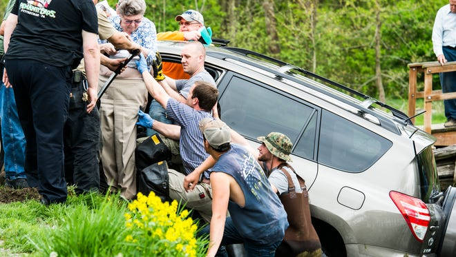 Fire crews from Myerstown Keystone Hook and Ladder help an elderly female from her SUV after it ended up in a pond at Limestone Springs in Jackson Township on Wednesday, April 26, 2017. A police report was not immediately available.
