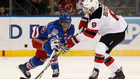 New Jersey Devils defenseman Will Butcher (8) passes the puck against New York Rangers defenseman Marc Staal (18) during the second period of an NHL hockey game game, Saturday, Oct. 14, 2017, in New York. (AP Photo/Julie Jacobson)