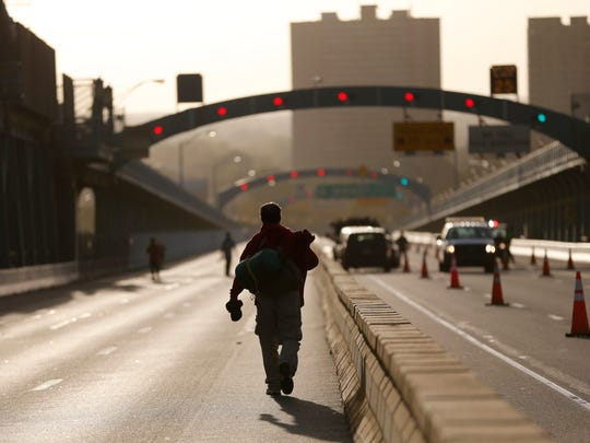 Alan Kurtz, of Burlington Township, N.J., walks over the Benjamin Franklin Bridge to New Jersey from Philadelphia, Sunday, Sept. 27, 2015, in Philadelphia. Kurtz, who saw Pope Francis during his papal parade in downtown on Saturday, made his way on foot on the bridge, which was shut down to vehicular traffic because of the pope's visit. (AP Photo/Julio Cortez)