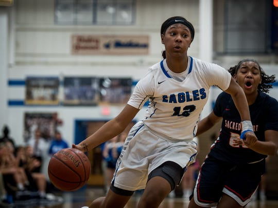 Eastern's Mikayla Kinnard (12) dribbles past  Sacred Heart's Kia Sivils (20) during the game at Eastern High School in Louisville, Kentucky, Saturday, December 13, 2017