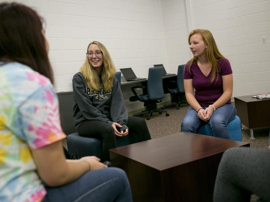 Blue Water Middle College students Danielle Duckworth, a Port Huron Northern graduate, and Brianna MacGregor, a Port Huron graduate, discuss their experience in the program with others Thursday in the Blue Water Middle College offices on the campus of St. Clair County Community College in Port Huron.