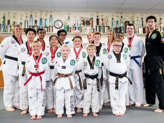 The 16 competition students at So's Taekwondo pose