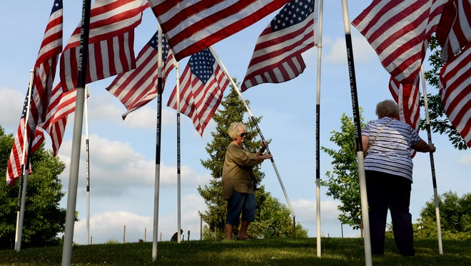 Susan Taylor-Wickham, Daughters of the American Revolution member and former USMC sergeant, places down a flag representing fallen USMC Lance Corporal Terry C. Wright during the Flags of Honor ceremony on Friday in Zanesville.