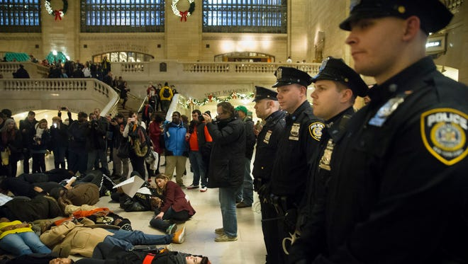"Police stand guard as protesters participate in a ""die-in"" at New York's Grand Central Station during a demonstration against a grand jury's decision not to indict the police officer involved in the death of Eric Garner on Dec. 6, 2014."