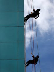 A mother and daughter rappel side-by-side down the