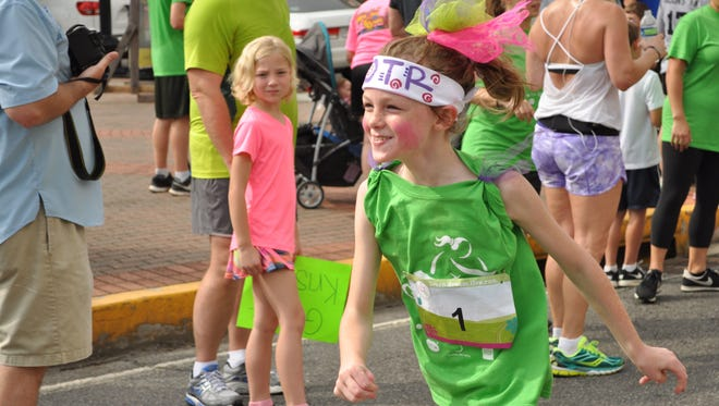 Maggie Coombs crosses the finish line of the YWCA's Girls on The Run 5K in downtown Alexandria.