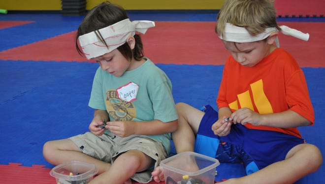"""Cooper Sims (left) and Lucas Hardy (right) take a Lego break during the """"Legos and Lightsabers"""" summer camp."""