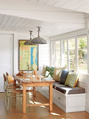 The farmhouse style uses vintage elements, such as the light fixtures in this window seating area, for a welcoming vibe.
