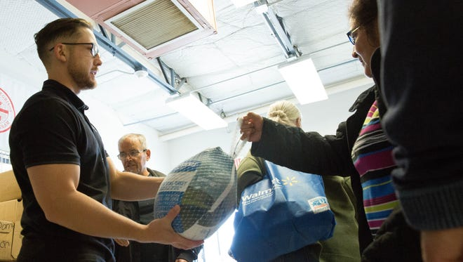 Kenny Valenzuela, left, the manager of the Las Cruces Convention Center, hands a frozen turkey to a client of Casa de Peregrinos Monday Nov. 20, 2017. Volunteers gathered to distribute all the fixings for a Thanksgiving Day meal to 1,529 clients.