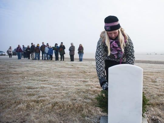 Kaydyn LeFurgey of Fort Benton places an initial wreath