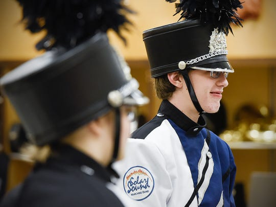 Marianna Coleman and Jacob Starren  try on their new Solar Sound marching band uniforms Thursday, March 15, at Technical High School.