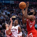 Toronto Raptors guard Greivis Vasquez, left, is knocked down by Houston Rockets guard James Harden, right, during a game in Toronto.