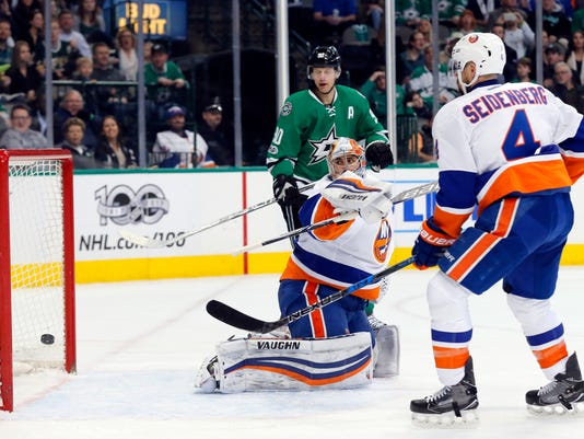 New York Islanders' Thomas Greiss (1) and Dennis Seidenberg (4) watch as a shot by Dallas Stars' Jamie Benn, not seen, goes in for a goal during  the first period of an NHL hockey game, Thursday, March 2, 2017, in Dallas. (AP Photo/Tony Gutierrez)