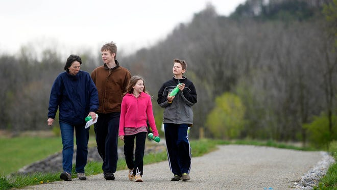 Dawn Balcom of Springettsbury Township walks with her children from left Henry Balcom, 16, Grace Balcom, 10, and Charles Balcom, 13, on the day of the official opening of a new section of the Heritage Rail Trail County Park in Springettsbury Township last year.