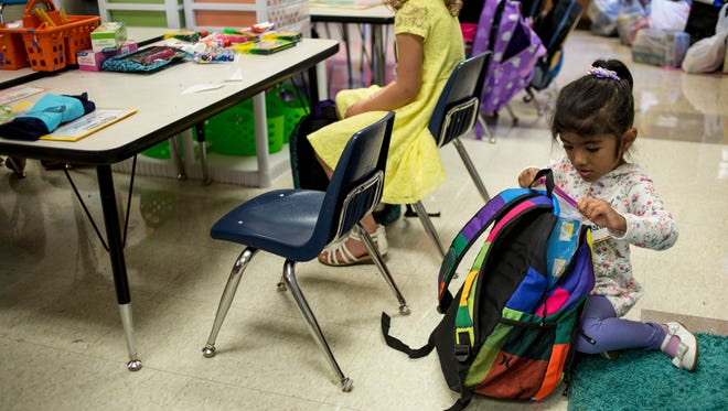 Kindergarten student Afshin Rabbani gets supplies out of her backpack Tuesday, September 6, 2016 at Keewahdin Elementary School in Fort Gratiot.