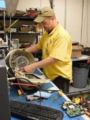 IdleAir employee Roger Wright repairs one of the company's