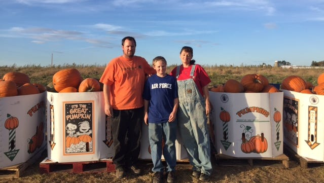 Mike Lawrence, Mikey Lawrence, 14, and Laurie Lawrence stand in one of their four pumpkin fields. They expect to produce around 35,000 pumpkins this year.