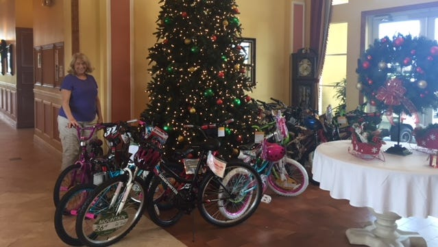 New bicycles and helmets crowd the Woodfield Clubhouse lobby awaiting to be picked up Dec. 16 by the U.S. Marines for the Toys for Tots program. This project was spearheaded by Sue Ackerman, pictured.