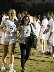 Eileen Wagner escorts her daughter Julia at the senior night ceremony.