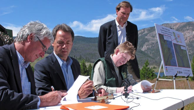 Montana Department of Natural Resources and Conservation Director John Tubbs, left, and U.S. Forest Service Regional Forester Leanne Marten, second from right, sign an agreement allowing the state to play a bigger role in forest management on federal lands as Montana Gov. Steve Bullock, center, and U.S. Agriculture Undersecretary Robert Bonnie, standing, look on outside Helena, Mont., Monday, July 18, 2016.